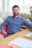 Smiling man with beard relaxing while working at home. Vertical of smiling man with beard relaxing while working at home Royalty Free Stock Photos