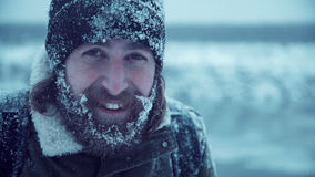 Smiling man with beard in snow Stock Photography