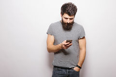 Smiling man with beard standing with  phone and texting. On white isolated background and holding mobile phone Royalty Free Stock Photo