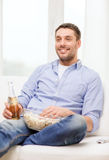 Smiling man with beer and popcorn at home Royalty Free Stock Image