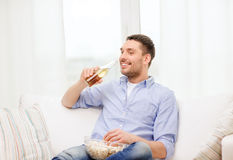 Smiling man with beer and popcorn at home. Home, technology and entretainment concept - smiling man with beer and popcorn at home stock images
