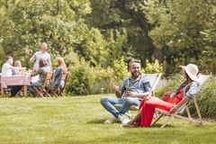 Smiling man with beer talking with friend while relaxing on sunbeds in the garden. Real photo. Smiling men with beer talking with friend while relaxing on royalty free stock photography