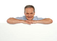 Smiling man behind blank white banner ad Royalty Free Stock Images