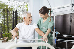 Smiling Man Being Assisted By Female Nurse In Using Walker. Smiling senior men being assisted by female nurse in using walker at rehab center royalty free stock images