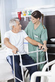 Smiling Man Being Assisted By Nurse In Using Zimmer Frame. Smiling senior men being assisted by female nurse in using Zimmer frame at rehab center royalty free stock image
