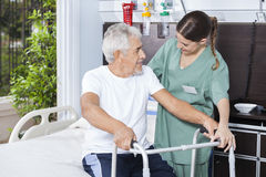 Smiling Man Being Helped By Nurse In Using Zimmer Frame Stock Images