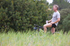 Smiling man with bicycle holding water bottle in rural field Royalty Free Stock Images