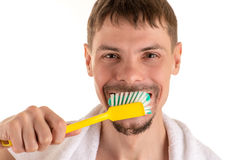 Smiling man with big yellow toothbrush in hand and white towel on his shoulders. Portrait of adult smiling man with big yellow toothbrush in hand and white towel Stock Images