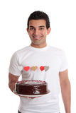 Smiling man with a birthday cake. Smiling man holding a chocolate birthday cake Royalty Free Stock Photography