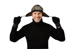 Smiling man in black dressed in warm clothes and cap. With ear-flaps isolated on the white background Stock Photos