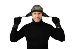 Smiling man in black dressed in warm clothes and cap. With ear-flaps isolated on the white background Royalty Free Stock Image
