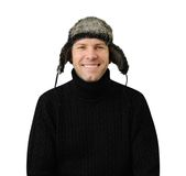 Smiling man in black dressed in warm clothes and cap. With ear-flaps isolated on the white background Stock Photo