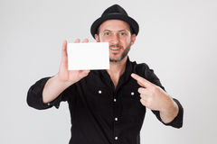 Smiling man in black shirt and black hat holding and pointing blank card Stock Image