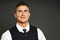 Smiling man in black vest. Portrait of young smiling man in black vest, right you can write some text Royalty Free Stock Image