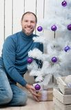 Smiling man in blue near a Christmas tree Royalty Free Stock Photography
