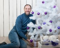 Smiling man in blue near a Christmas tree Stock Photography