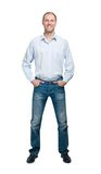 Smiling man in blue shirt and jeanse isolated on white backgroun Stock Image