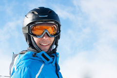 Smiling man in the blue skiing jacket, helmet and glasses against cloudy sky Stock Photography