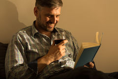 Smiling man with book. Smiling man reading interesting book in bed Royalty Free Stock Photos