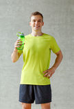 Smiling man with bottle of water in gym Royalty Free Stock Image