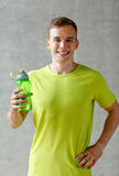 Smiling man with bottle of water in gym Royalty Free Stock Images