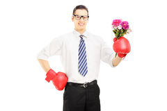 Smiling man with boxing gloves holding a bunch of flowers Royalty Free Stock Photos
