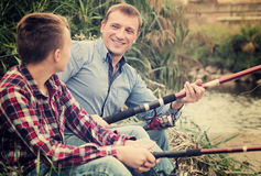 Smiling man and boy fishing together on river Stock Images