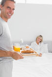 Smiling man bringing breakfast in bed to his partner Stock Photos