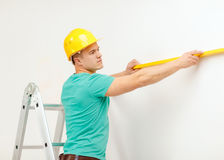 Smiling man building using spirit level to measure Royalty Free Stock Photography
