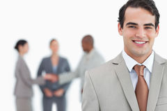 Smiling man of business with trading partners behind him Royalty Free Stock Photography