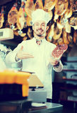 Smiling man butcher showing piece of meat. In butcher's store Stock Photos