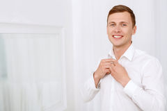 Smiling man buttoning up to neck white shirt. Finishing with smile. Smiling man buttoning up to neck white shirt against white background Royalty Free Stock Photography
