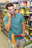 Smiling man buy food and phoning Stock Image