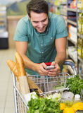 Smiling man buy products and using his smaprtphone Stock Photos
