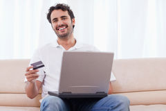 Smiling man buying online Stock Photography