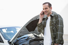 Smiling man calling for assistance after breaking down Stock Photos