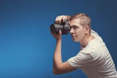 Smiling Man with camera isolated on blue background. Young man holding digital camera and making photo looking on side. Lifestyle. Travel and technology royalty free stock image