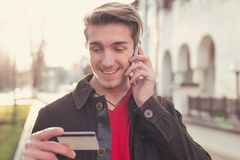 Smiling man with card talking on phone Royalty Free Stock Images