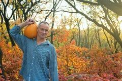 Smiling man carries pumpkin Stock Photo