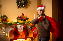 Smiling man carrying big Santa bag with gifts on Christmas eve Royalty Free Stock Photos