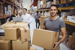 Smiling man carrying box Royalty Free Stock Images