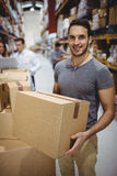 Smiling man carrying box Royalty Free Stock Photography
