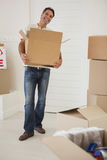 Smiling man carrying boxes in new house Stock Photography