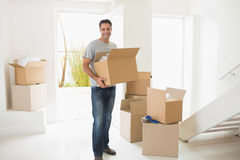 Smiling man carrying boxes in a new house Royalty Free Stock Images