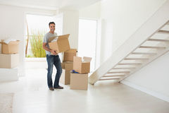 Smiling man carrying boxes in a new house Royalty Free Stock Photography