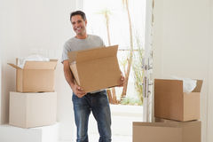 Smiling man carrying boxes in new house Stock Images