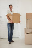 Smiling man carrying boxes in new house Royalty Free Stock Photo