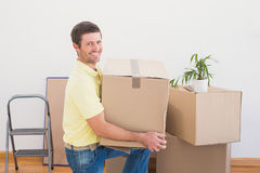 Smiling man carrying cardboard moving boxes at home Stock Image