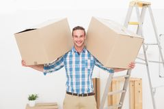 Smiling man carrying cardboard moving boxes Stock Images