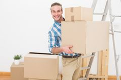 Smiling man carrying cardboard moving boxes Royalty Free Stock Photo